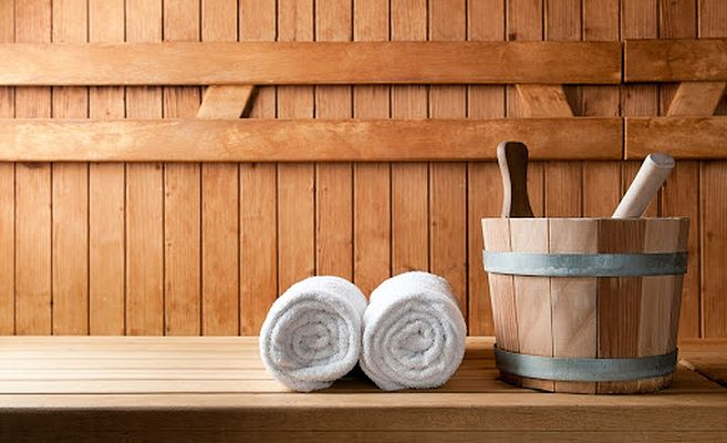 towels and traditional sauna bucket in sauna used in sweat rituals